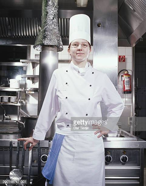 female chef in kitchen, smiling, portrait - main sur la hanche photos et images de collection
