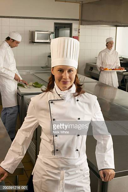 Female chef in kitchen, smiling, portrait, two cooks in background