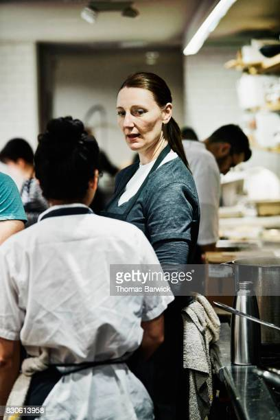 Female chef leading team in dinner preparation in restaurant kitchen