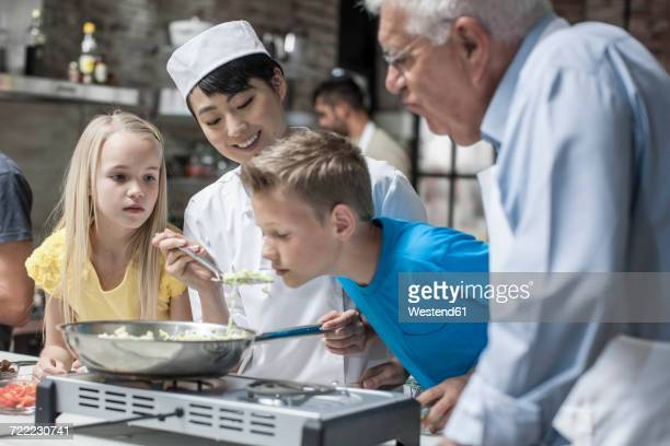 Female chef letting child smell from frying pan