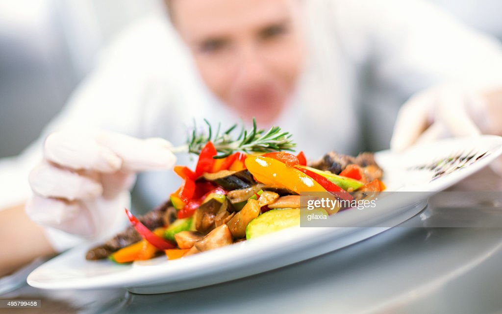 Female chef places finishing touches on meal. : Stock Photo