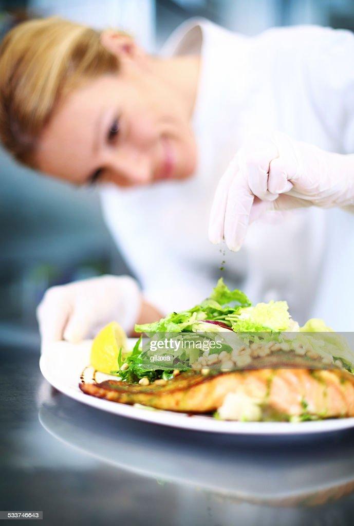 Femmina chef luoghi tocchi al pasto. : Foto stock