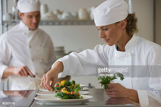 Female chef plating food