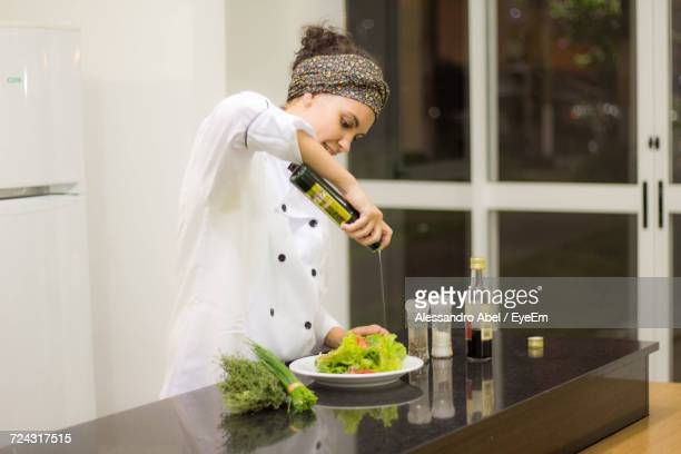 Female Chef Pouring Olive Oil On Salad While Standing In Commercial Kitchen