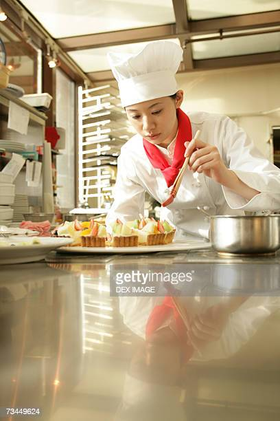 Female chef preparing a strawberry tart in a restaurant