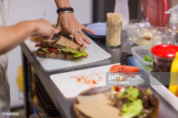 Female chef preparing sandwiches in a cafe kitchen