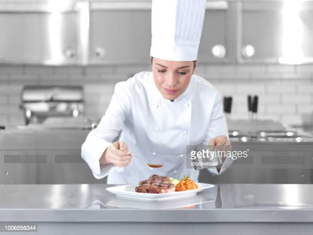 female chef preparing steak plate - chef stock pictures, royalty-free photos & images