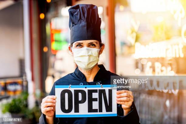 female chef restaurant owner posing wearing a mask holding an open sign - open sign stock pictures, royalty-free photos & images
