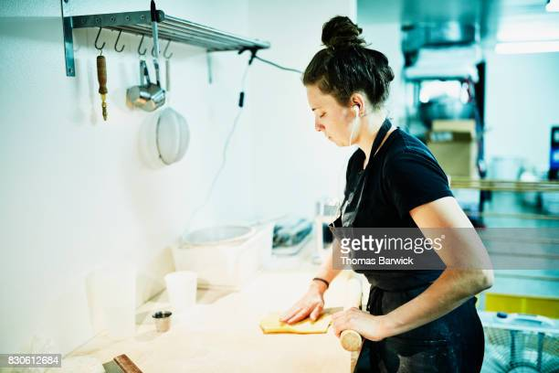 Female chef rolling dough for fresh hand made pasta