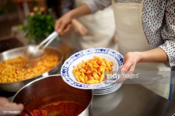 female chef serving pasta in a plate - italian culture stock pictures, royalty-free photos & images