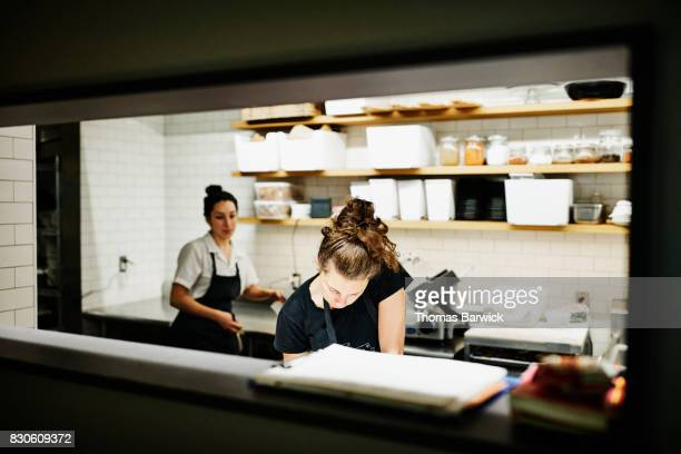 Female chef taking notes in kitchen before dinner meal service