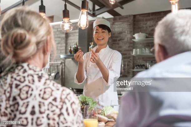 Female chef talking to senior couple in cooking class