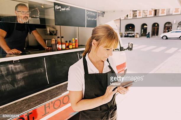 Female chef using mobile phone by food truck at city street