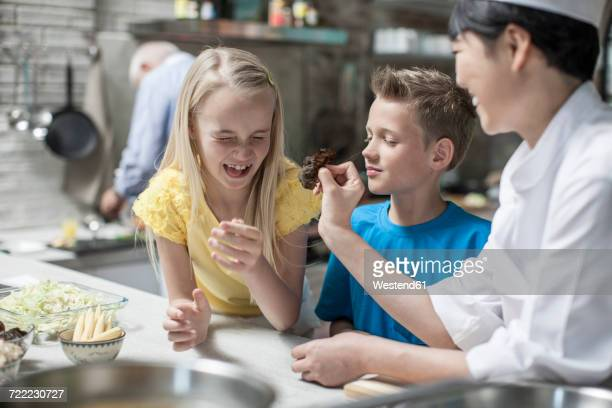 Female chef with girl pulling faces in cooking class