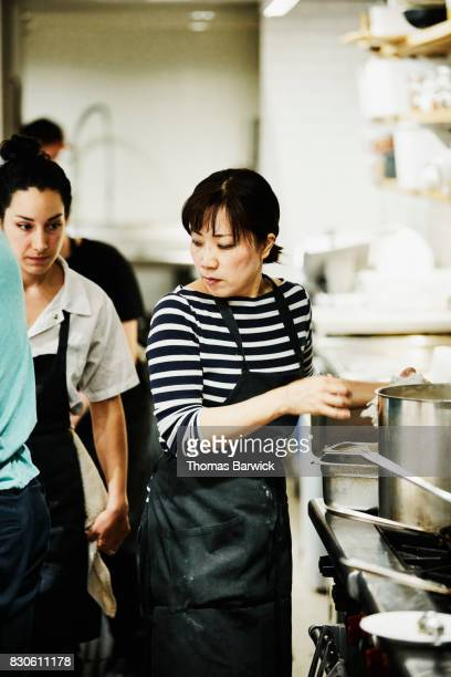Female chef working at stove in crowded kitchen preparing for dinner service