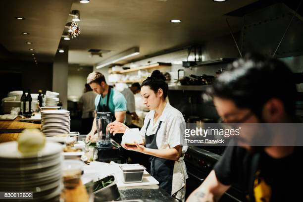 Female chef working with block of Parmesan cheese while preparing for dinner service in restaurant kitchen