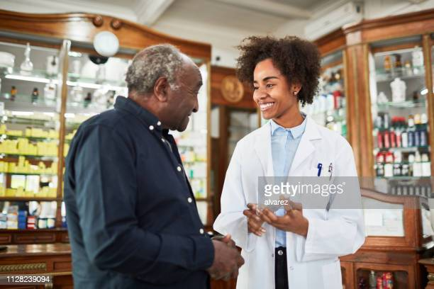 female chemist assisting senior customer - customer focused stock pictures, royalty-free photos & images