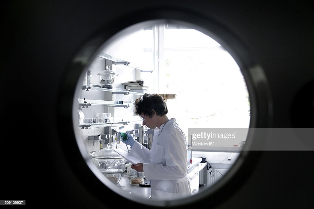 Female chemist working in lab watched through spy hole : Stock Photo