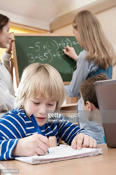 Female childcare assistant helping children by doing homework