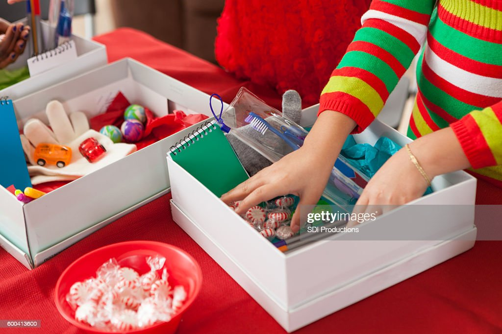 Female children filling holiday donation boxes for children in need : Stock Photo