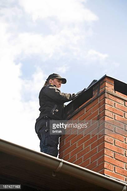 Femme sur le toit-Cheminée-brich nettoyage d'une cheminée.