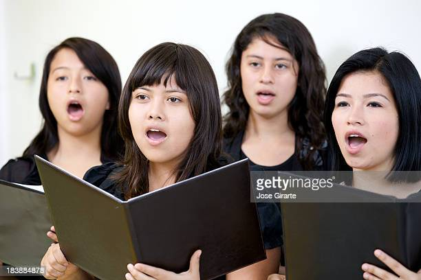 Female choir singing while holding open music books