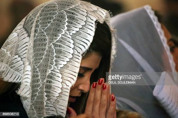 Female Christian worshippers attend Christmas day mass at the Syriac Orthodox Church of Mar Dodo in the northeastern Syrian Kurdish town of Derik...