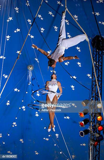 Female Circus Acrobat Hangs From the Mouth of a Male Circus Acrobat, High Up in a Circus Tent, Twirling a Ribbon Around Herself
