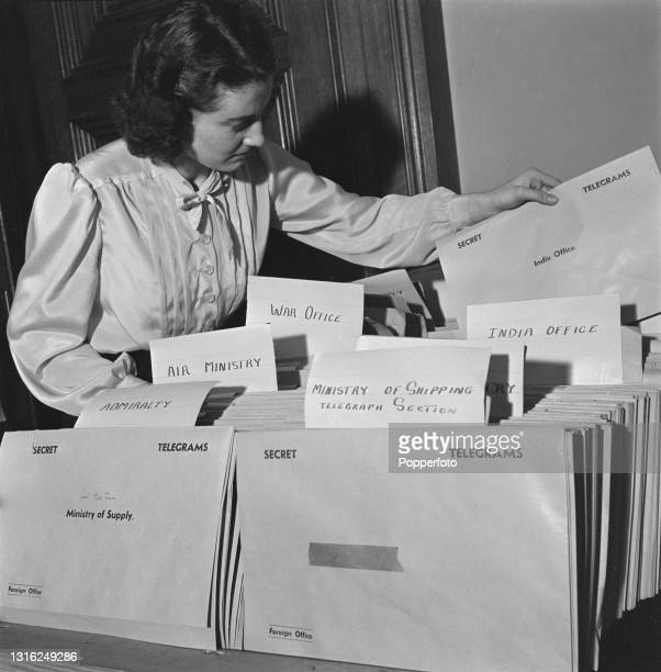Female civil servant sorts secret incoming telegrams addressed to various government departments in the Distribution Office at the Foreign and...