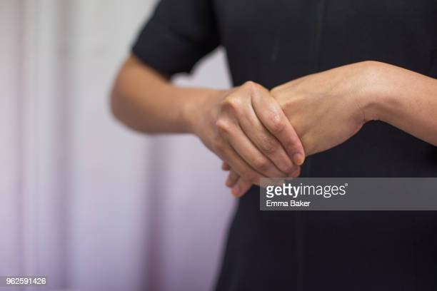 female clasping hands - emma baker stock pictures, royalty-free photos & images