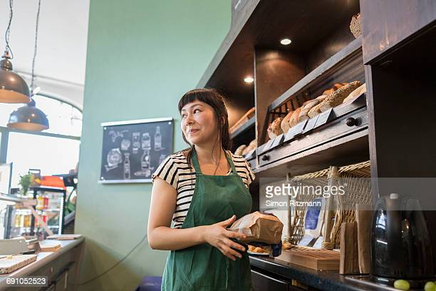 Female clerk at bread counter in grocery store