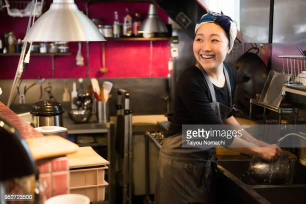 a female clerk who enjoys conversation while washing tools - happy merchant stock pictures, royalty-free photos & images