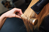 Female client in beauty salon. Close-up of hairdressers hand drying blond hair with hair dryer and round brush, doing new hairstyle
