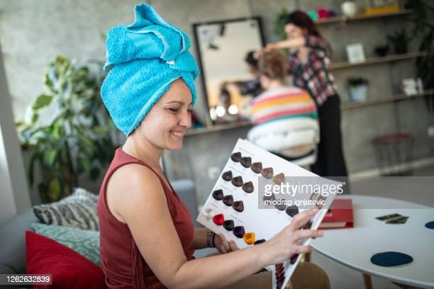 ヘアサロンでカタログから髪の色を選択する女性クライアント - 染料 ストックフォトと画像