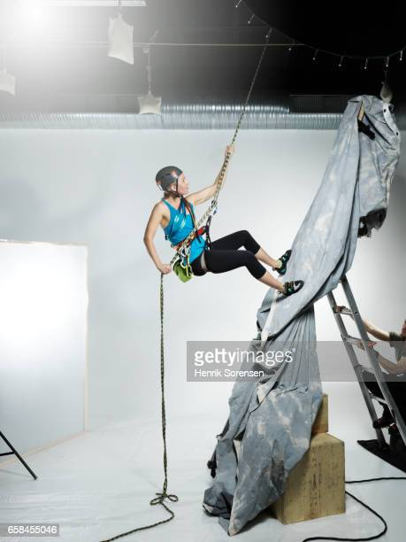Female climber abseiling in a studio
