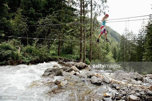 Female climber balancing on rope over river