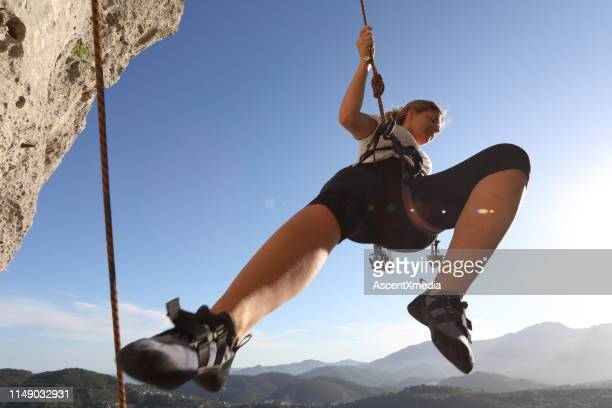 female climber bounces off rock face as she is belayed down route - play off stock pictures, royalty-free photos & images