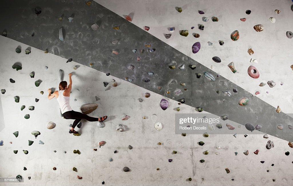 Female climber clinging to climbing wall : Stock Photo