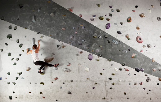 Female climber clinging to climbing wall - gettyimageskorea
