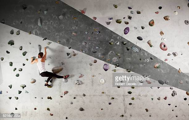 female climber clinging to climbing wall - vastberadenheid stockfoto's en -beelden