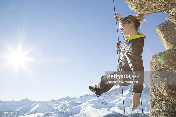 Female climber dangles from rope, looks towards sun