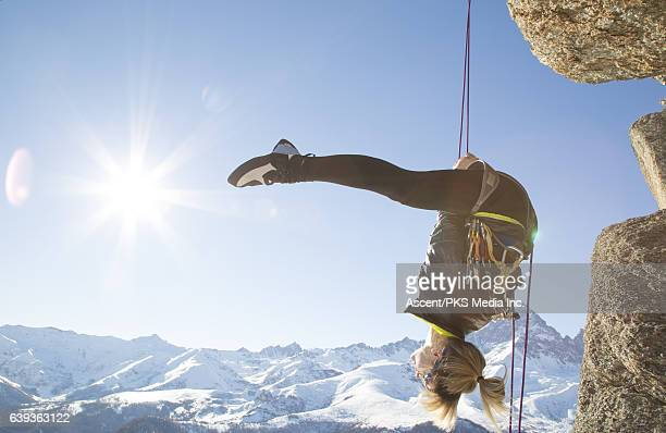 Female climber dangles from rope, performs gymnastic feat