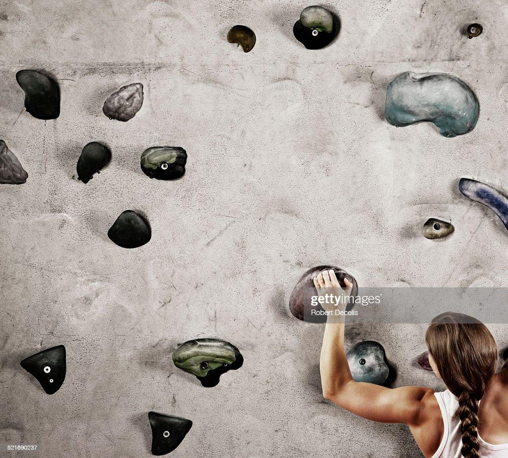 Female climber holding onto hold on climbing wall : Stock Photo