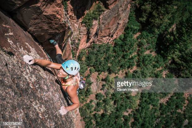 female climber holds crimpers but stays focused high on the wall - bookend stock pictures, royalty-free photos & images