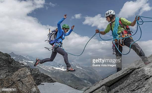 Female climber jumping between rocks