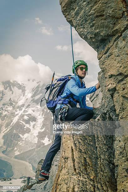 female climber on a rocky wall - scalare foto e immagini stock