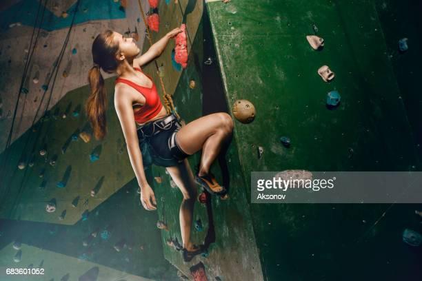 Female climber purposeful climbs up the indoor climbing wall