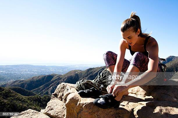 a female climber puts on her climbing shoes while sitting on top of lower gibraltar rock in santa barbara, california. lower gibraltar rock provides great vistas of santa barbara and the pacific ocean. - lady barbara stock-fotos und bilder