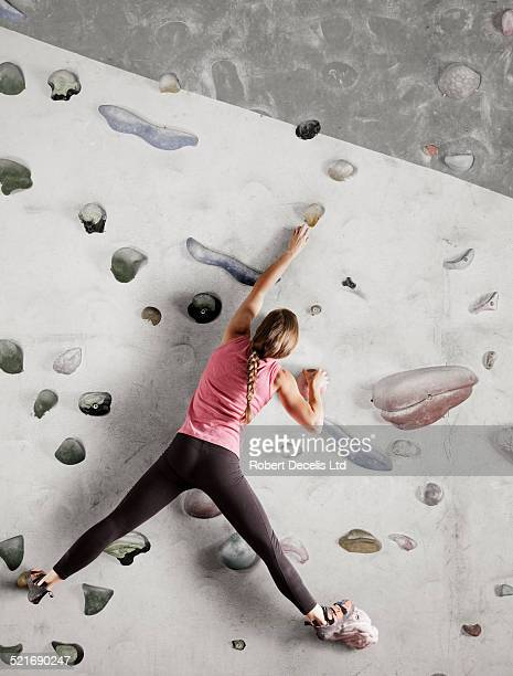 Female climber reaching for hold on indoor wall