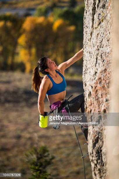 female climber reaching into chalk bag while climbing, wyoming, usa - chalk bag stock pictures, royalty-free photos & images